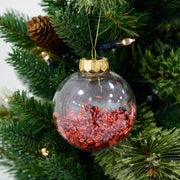 red foil filled shaker with gold thread and top hanging from a christmas tree