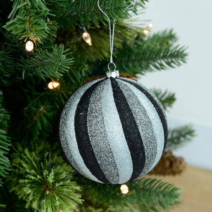 black and silver glitter bauble hanging from a christmas tree with led lights