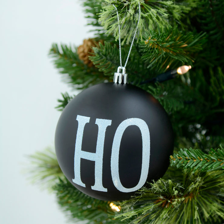 Black 'Ho' design tree bauble hanging from a pre-lit christmas tree