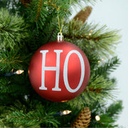 single red 'Ho' bauble on christmas tree with led lights