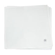 white napkin set with embroidered silver leave detail in the corner