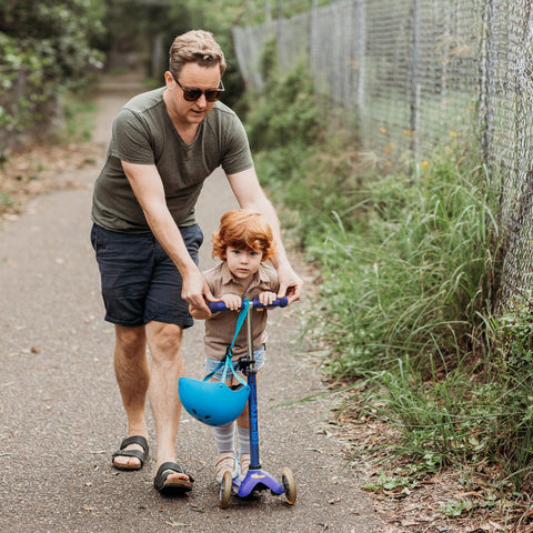 Dad and child scooting together on Mini Micro Deluxe