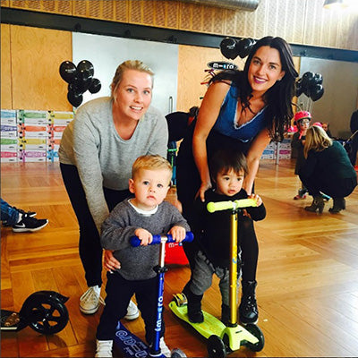 Sarah Coles and Amber Vito with their sons on Mini Micro Deluxe scooters