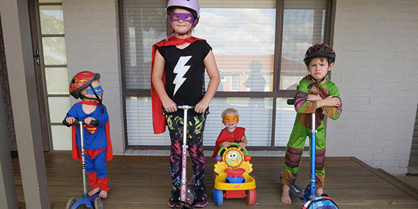 Kids dress up as scooting super heroes