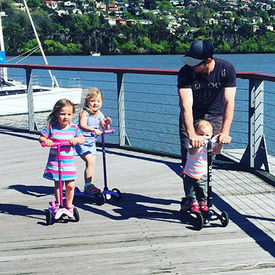 Dad and daughters scooting