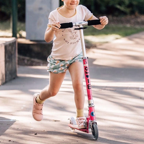 girl on micro sprite scooter