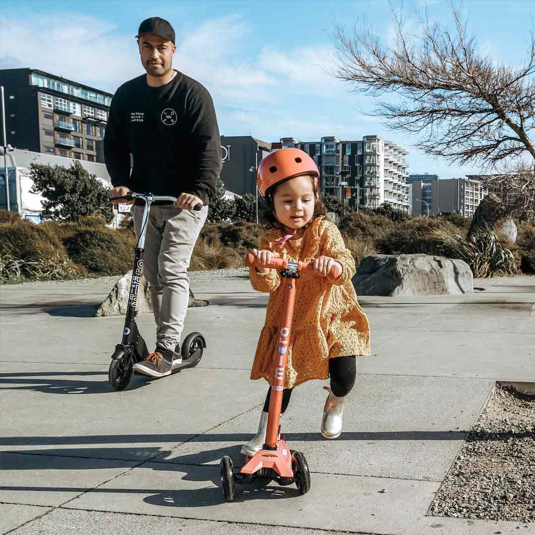 little girl and her dad scooting to school