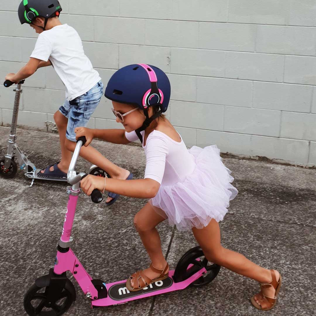 brother and sister on their 2 wheel scooters going to school