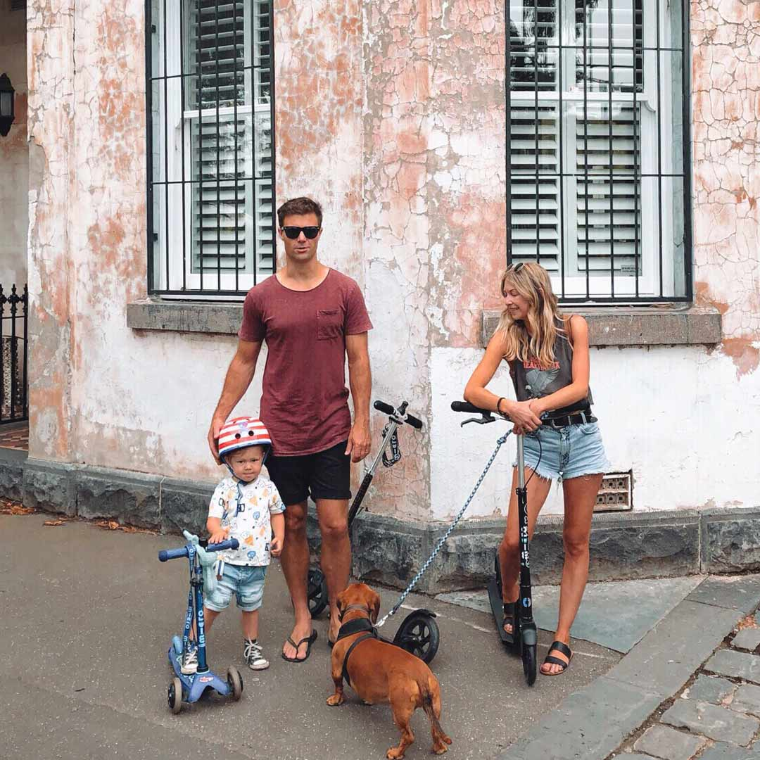 Parents & kid with Micro scooters and dog