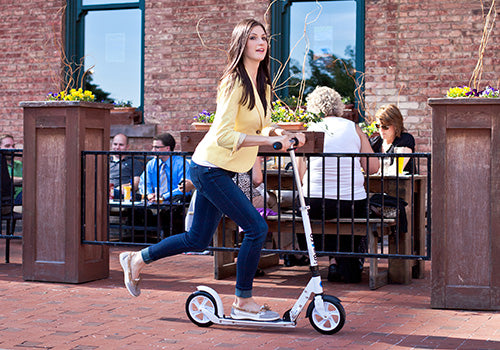 Woman using kick scooter to travel