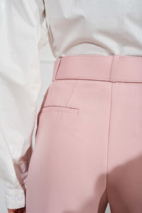 Pink pants with tucks at the waist and a wide belt