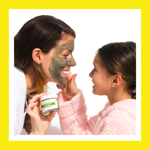 woman wearing face mask with girl touching her face