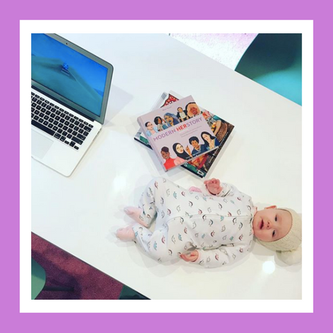 Baby laying on a table next to a laptop and stack of books