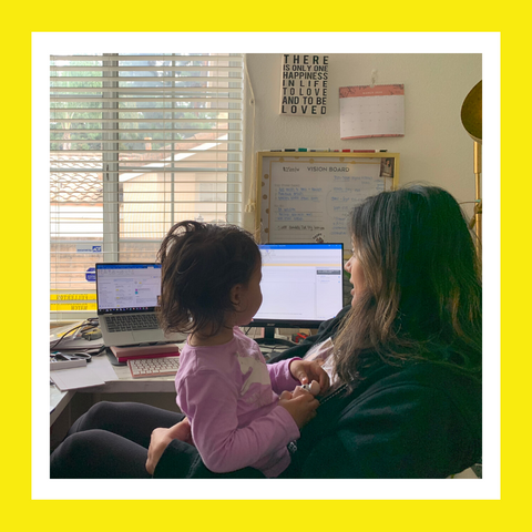Woman sitting at a desk with her daughter while working
