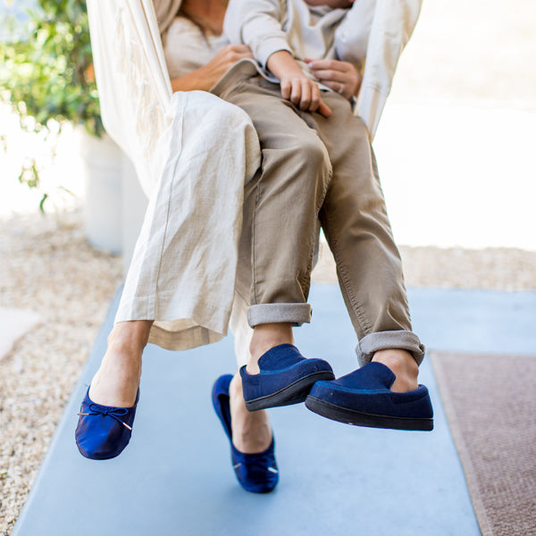 Women wearing Sloan Ballerina slippers with her son in the Kid's Chandler Moc. Both sitting in a hanging chair, laughing