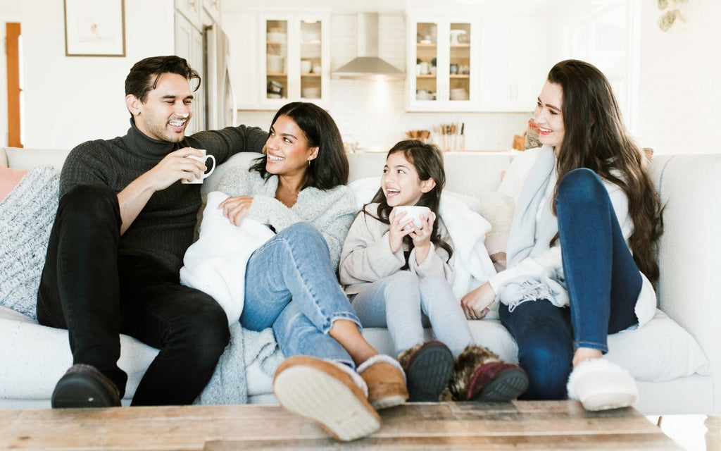 Family sitting on a sofa in their Isotoner slippers, Laughing and enjoying each other's company