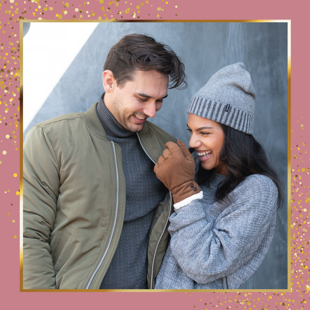 Male and Female model laughing. Female model wearing Recycled microsuede gloves and knit hat. Set on a mauve background with gold framing and gold sparkles