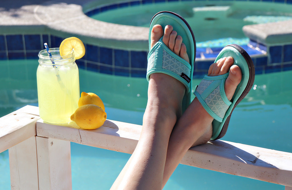 Mesh Mia Thong Slippers on figure sitting at a pool with a glass of lemonade