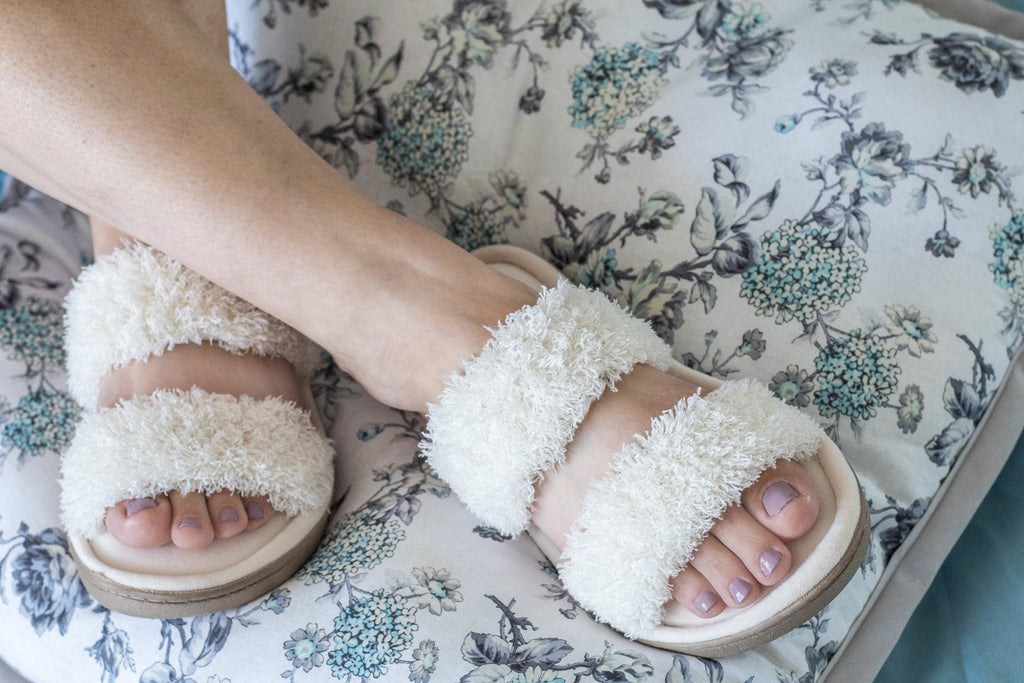 Chenille Parker 2-Band Slide Slippers on figure sitting on a pillow