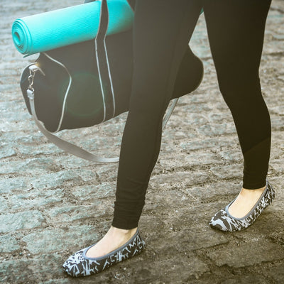 Women's Paris Travel Ballerina Slippers in Ash Geo Print on model walking down the street with gym bag and yoga mat in hand