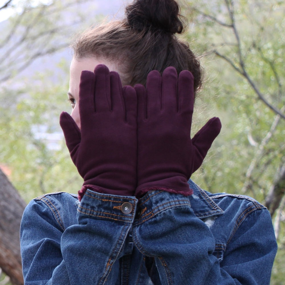 Women's Stretch Fleece Gloves in Plum on model in front of her eyes standing in a forest