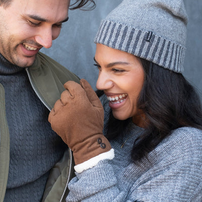 Women's Recycled Microsuede Gloves in Cognac on figure. Female model laughing while wearing gloves and Isotoner Recycled Cap with male model smiling next to her