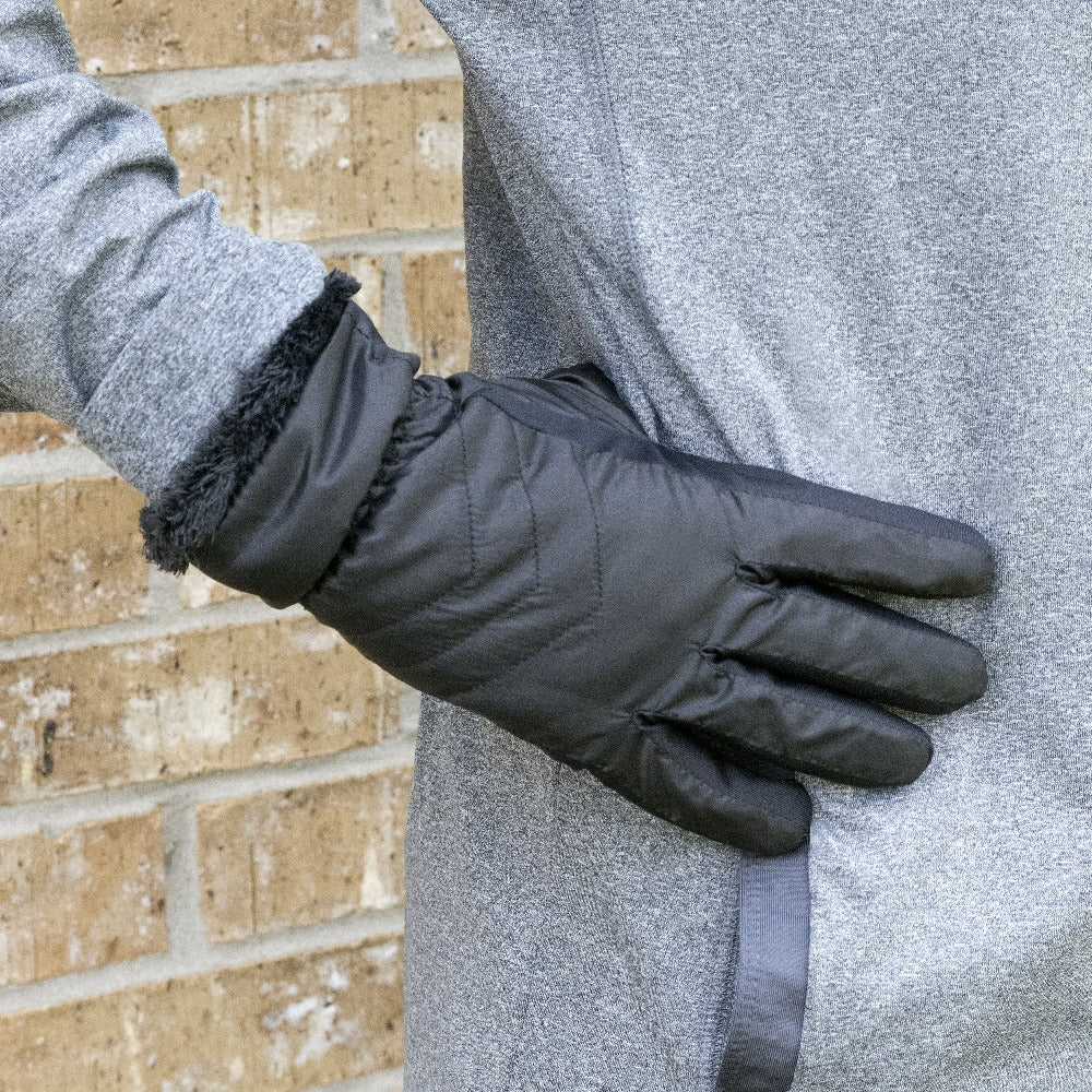Women's SleekHeat™ Quilted Gloves in Black on figure. Model wearing performance clothing with her gloved hand on her hip against a brick wall