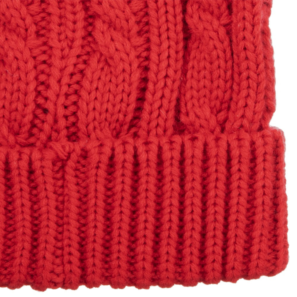 Close up texture view of womens soft knit cable beanie hat in really red