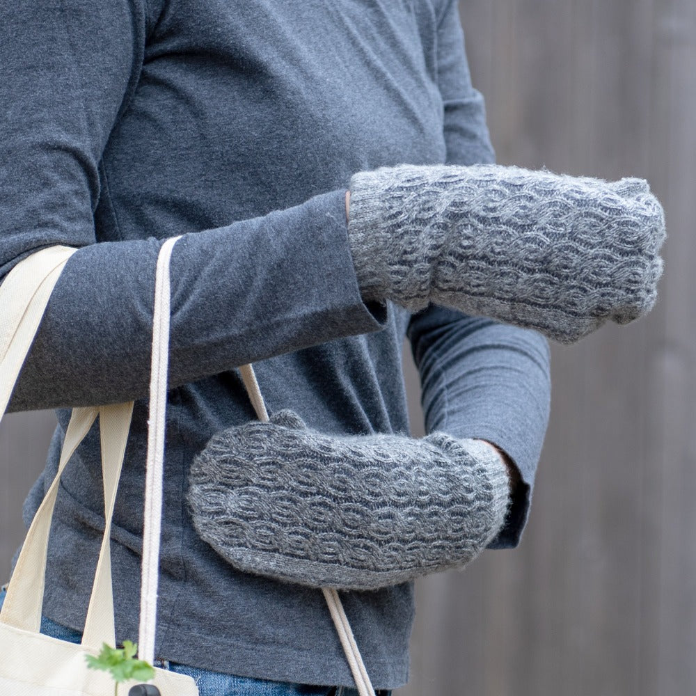 Women's Recycled Fine Gauge Cable Knit Mittens in Dark Charcoal Heather Grey on figure. Model wearing gloves and holding a reusable tote bag