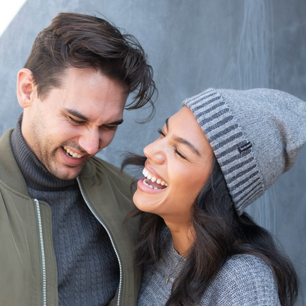 Women's Recycled Fine Gauge Knit Hat in Grey on figure. Model wearing hat while laughing with male model