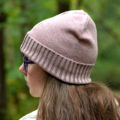 Women's Recycled Fine Gauge Knit Hat in Wild Blossom Pink on figure. Model standing in a wooded area wearing the hat