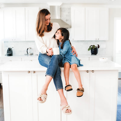 Signature Women's Microterry with Satin X-Slide Slippers on figure. Mom wearing the x-slides, holding a cup of coffee and snuggling her daughter who sits next to her on the kitchen counter
