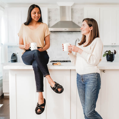 Signature Women's Microterry with Satin X-Slide Slippers in black on figure. Two female models talking over coffee. One sitting on the kitchen counter wearing her black x-slides.