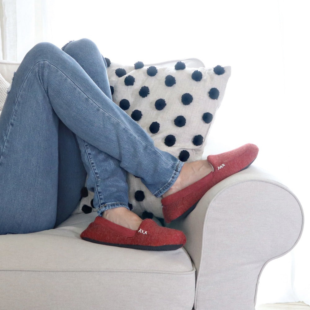 Women's Microsuede Marisol Moccasin Slippers in Red Brick on Model with Feet up the arm of a chair