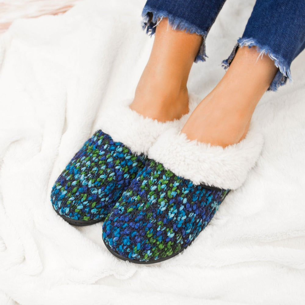 Women's Sweater Knit Amanda Hoodback Slippers in Navy Blue with green on Model laying in blankets