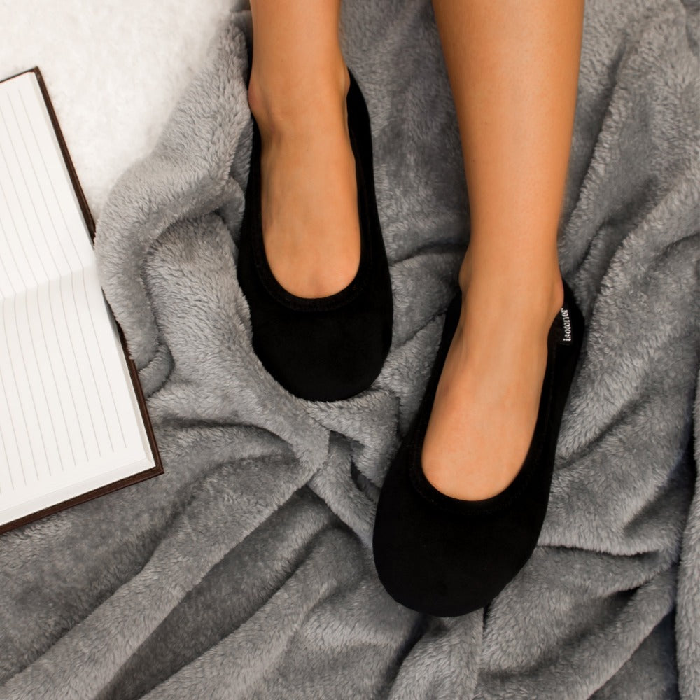 Women's Velour Victoria Ballerina Slippers in Black on model surrounded by cozy blankets