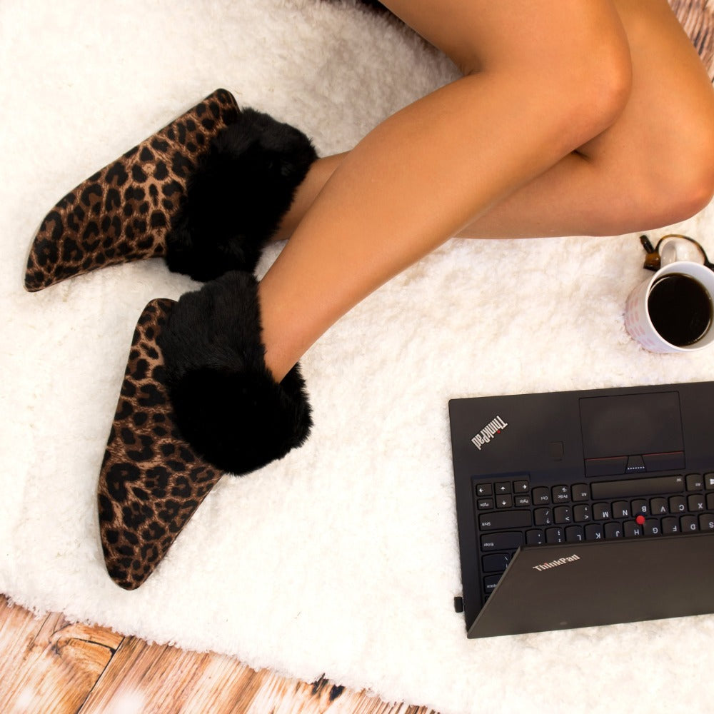 Women's Stretch Velour Sabrine Bootie Slippers in Cheetah on Model sitting on the floor working on a laptop