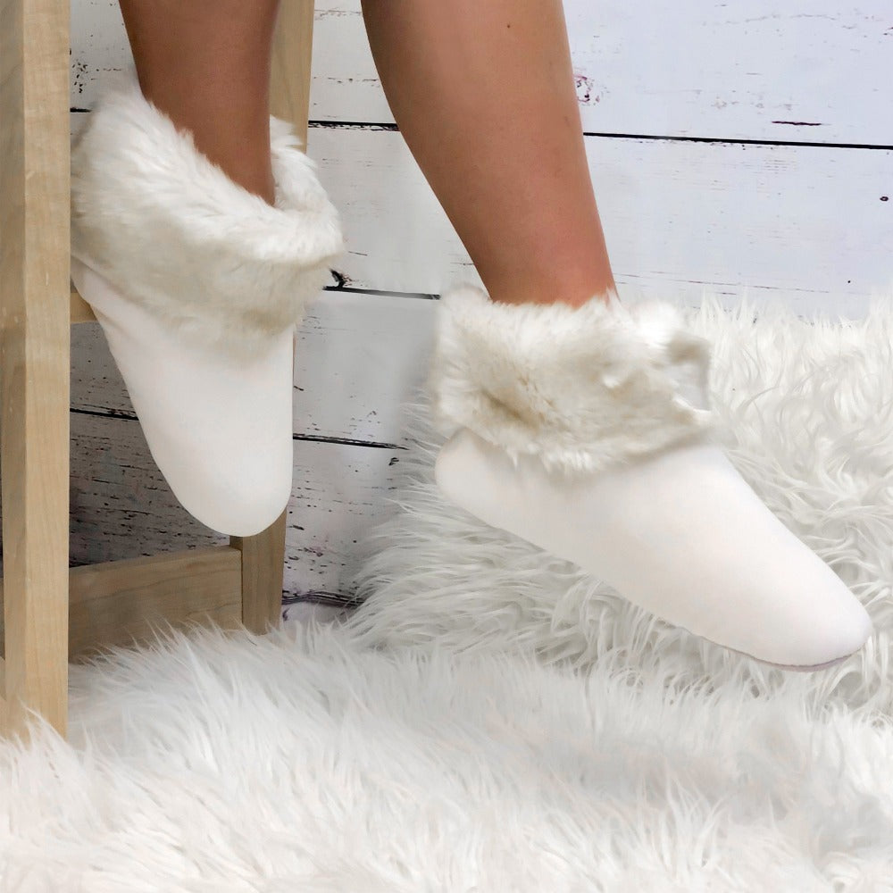 Women's Stretch Velour Sabrine Bootie Slippers in Ewe on Model sitting on stool around a fur rug