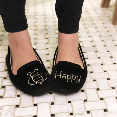 "Women's Velour Conversational Smoking Slippers Pair in Black one slipper has an illustration of a Bee the other says ""Happy"" on Model standing on a tile floor"
