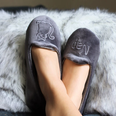 "Women's Velour Conversational Smoking Slippers Pair in Mineral one slipper has an illustration of a Cat, the other says ""Nap"" on Model with her feet up"