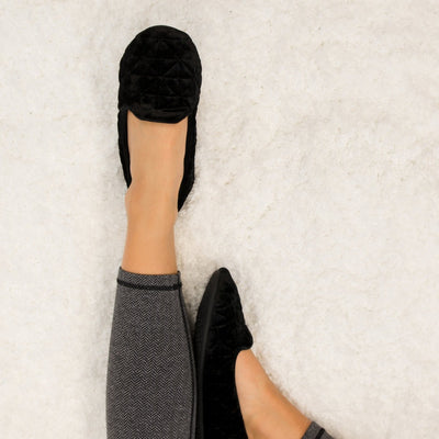 Women's Stephanie Crushed Velour Closed Back Slippers in Black on Model Laying on Fur Rug