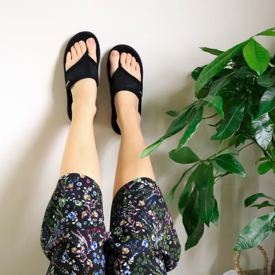 Women's Mesh Mia Thong Slippers in Black on model up against a white wall with greenery to the right side.