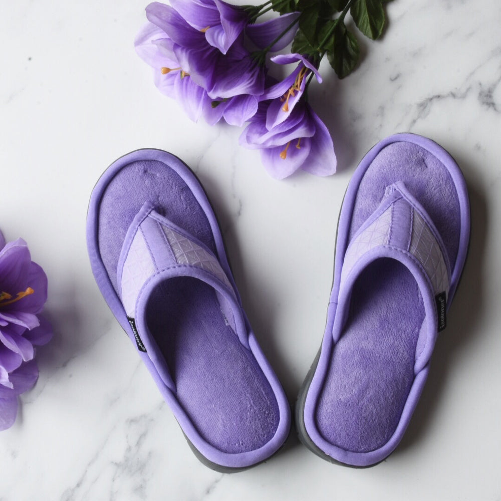 Women's Mesh Mia Thong Slippers in Paisley Purple on marble backdrop with purple flowers around