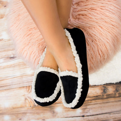 Women's Microsuede Alex Moccasin Slippers in Black On Model Feet propped up on stool