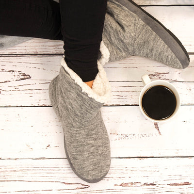 Women's Marisol Boot Slippers in Heather Grey on Model sitting on hardwood floor with cup of coffee