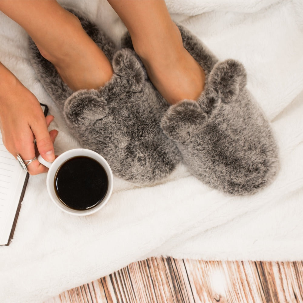 Women's Faux Fur Fey Novelty Hoodback Slippers in Dark Chocolate Bear on Model on Fur Rug with Coffee Mug