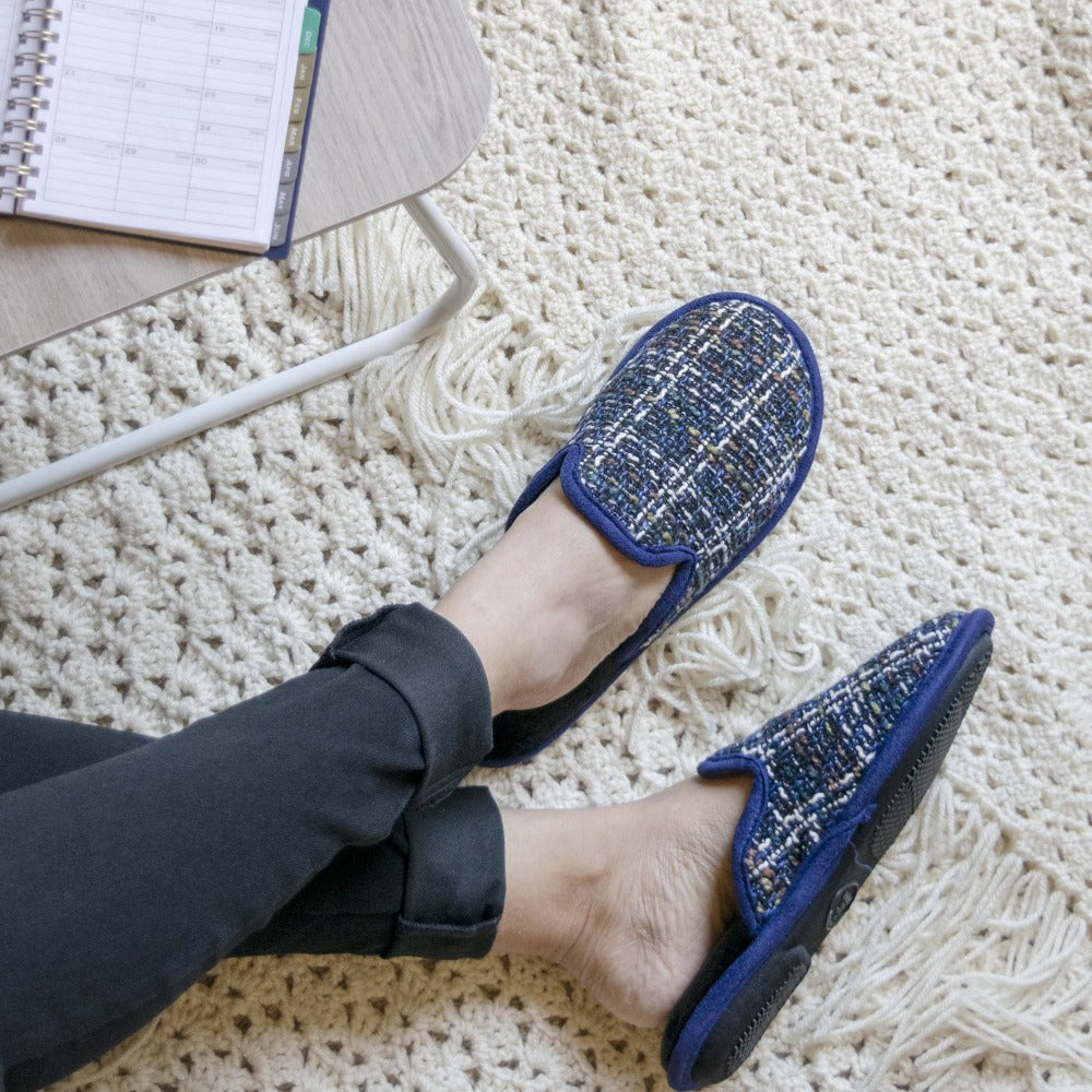 Women's Tweed Kaitlyn Scuff Slippers in Steele Blue on model sitting down on a quilted blanket filling in a day planner