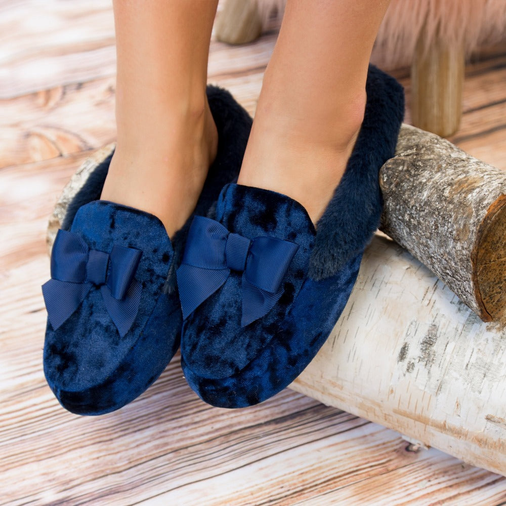 Women's Iridescent Velour Krista Hoodback Slippers in Navy Blue on Model Slippers resting on logs
