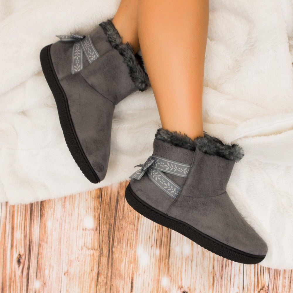 Women's Microsuede Addie Boot Slippers with Bow in Ash On Model laying on plush blanket on hardwood floor