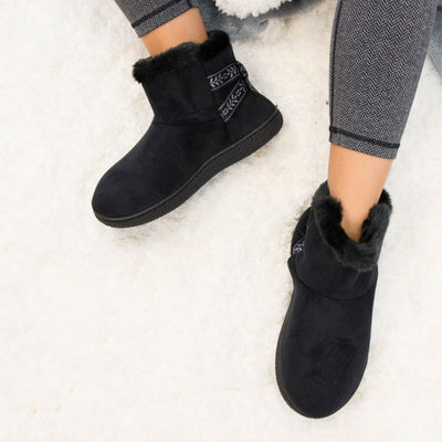Women's Microsuede Addie Boot Slippers with Bow in Black on model on plush fur rug
